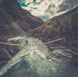 Aerial view of woman standing on the suspension bridge over a wild mountain river. Royalty Free Stock Images