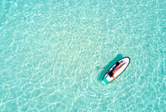 Aerial view of a woman on a surfboard in the turquoise waters Stock Photos