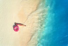 Aerial view of woman with swim ring on the sandy beach. Aerial view of the beautiful young lying woman with pink donut swim ring on the white sandy beach near stock photo
