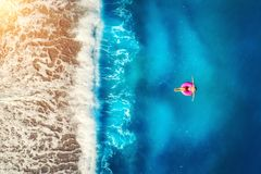 Aerial view of woman swimming on the pink swim ring in the sea Stock Photography