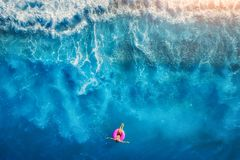 Aerial view of woman swimming on the pink swim ring in the sea Royalty Free Stock Image