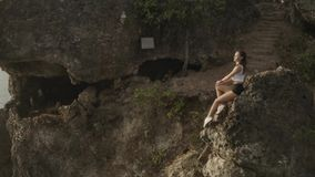 Aerial view of woman taking break after morning jogging on sea shore cliff at sunrise. Aerial drone view of young attractive woman taking break after morning stock footage