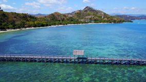 Aerial view of wooden pier in Labuan Bajo. Exotic aerial view of wooden pier with turquoise sea water in Labuan Bajo, Flores Island an island located close to stock footage