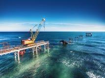 Aerial view of work crane on the broken bridge. Aerial view of working crane on the broken bridge Stock Photo