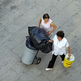 Aerial view of working cleaning women, Portugal. Polish women walking with a garbage truck over a square. One woman also carries an empty tin of oil. To be Royalty Free Stock Photography