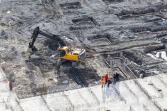 Aerial view of working excavator with builders stand near Royalty Free Stock Photos