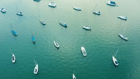 Aerial view of yacht cub and marina on sunny day. Yacht and sailboat is moored at the quay. Fly over stock footage