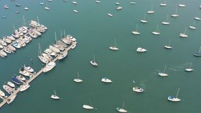 Aerial view of yacht cub and marina on sunny day. Yacht and sailboat is moored at the quay. Tilt stock video