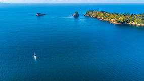 Aerial view on a yacht racing along tiny island ocean on sunny day. Coromandel Peninsula, New Zealand Stock Image