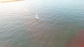 Aerial view of yacht sailing away from coast on a bright sunset with sunny flares and rays