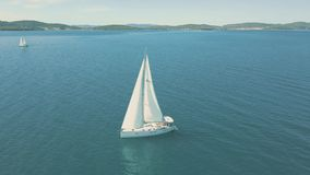 Aerial view of yacht sailing near beautiful Islands. Beautiful clouds in the background stock video footage