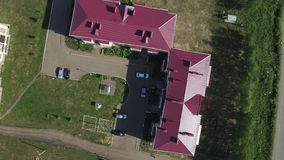 Aerial View Yard between Red Roofs Houses. Aerial view shady yard between red roof houses with lawns trees car parks camera removes upward to sunny cityscape stock video footage