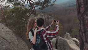 Aerial view of a young adorable people taking selfie on the top of the mountain, smiling, and laughing. Gorgeous scenery stock footage