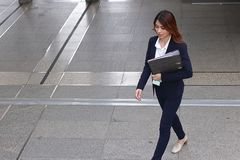 Aerial view of young attractive Asian business woman holding document folder and walking on flooring in the city against copy spac Stock Photo