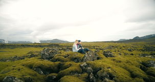 Aerial view of young beautiful couple sitting and enjoying the landscape of lava field in Iceland. Copter flying around.