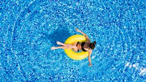 Aerial view of young brunette woman swimming on the inflatable big yellow in the pool. Top view of slim lady relaxing on her holid stock photo