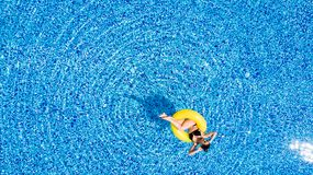 Aerial view of young brunette woman swimming on the inflatable big yellow ring in pool royalty free stock image