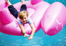 Aerial view of young caucasain boy floating in the pool with fla. Mingo shape inflatable tube royalty free stock images