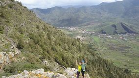 Aerial view of young couple on a mountain ridge waving hands. Amazing mountain landscape in Tenerife, Canary Islands. Aerial view of young couple on a mountain stock footage