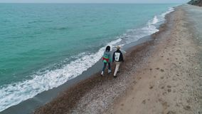 Aerial view of young couple walk on beach.  stock video footage
