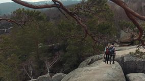 Aerial view of young couple wandering together, climbing down from the top of the rocky mountain, holding their hands stock video footage