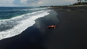 Aerial view of young girl. Black sand beach at Bali island in Indonesia. Black sand beach at Bali island in Indonesia stock footage