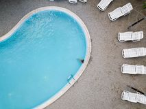 Aerial view of a young girl in black swimsuit, blue swimming pool and white sunbeds stock images