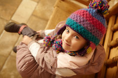 Aerial View Of Young Girl Sitting On Wooden Seat. Aerial View Of  Young Girl Sitting On Wooden Seat Putting On Warm Outdoor Clothes And Boots Looking Up To Stock Images