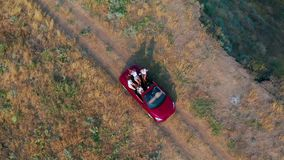 Aerial view. Young girls driving convertible car at sunset by the sea front beach. Summer adventure. stock footage