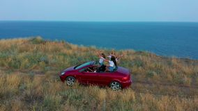 Aerial view. Young girls driving convertible car at sunset by the sea front beach. Summer adventure. stock video footage