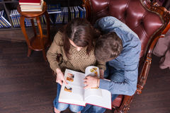 Aerial View of Young Lovers Reading a Book. Aerial View of Young Sweet Lovers Reading a Book at the Library While Sitting on the Chair so Closed Stock Photography