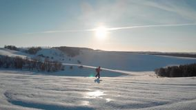 Aerial view young man hiking on top of snowy mountain at beautiful winter sunset. Male mountaineer with trekking poles stock video footage