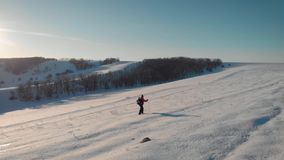 Aerial view young man hiking on top of snowy mountain at beautiful winter sunset. Male mountaineer with trekking poles stock video