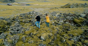 Aerial view of young stylish couple walking through the volcanic lava field in Iceland. Man and woman go to their car. Family, man and woman enjoying the stock footage