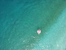 Aerial view young woman on giant inflated flamingo float in turquois water of Ionian Sea Albania.  royalty free stock photography