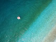 Aerial view young woman on giant inflated flamingo float in turquois water of Ionian Sea Albania.  stock image
