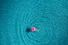 Aerial view of young woman swimming on the pink swim ring Royalty Free Stock Photos