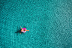Aerial view of young woman swimming on the pink swim ring Stock Image