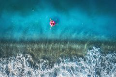 Aerial view of young woman swimming on the pink swim ring Stock Photo
