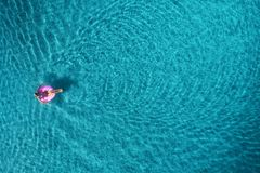 Aerial view of young woman swimming on the pink swim ring in the transparent turquoise sea at sunrise in Thailand. Summer seascape with girl, clear water in Royalty Free Stock Image