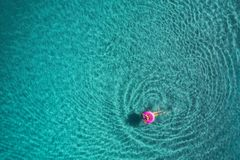 Aerial view of young woman swimming on the pink swim ring in the transparent turquoise sea at sunrise in Thailand. Summer seascape with girl, clear water in Stock Photography