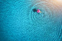 Aerial view of young woman swimming in the sea with transparent water Royalty Free Stock Image