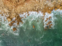 Aerial. Waves beat against the shore, the view from the sky. Stock Photo