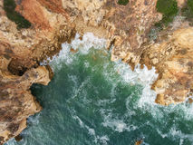 Aerial. Waves breaking to the rocky shore. Taken from the sky. Stock Images