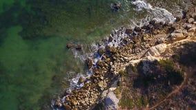 aerial Wellen waschen die Steine auf Ufer von Albufeira Olhos de Agua stock video footage