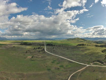 Aerial of Open Range Grazing Mountain. A kite aerial photo of a vast, agricultural area in Western Montana. A diagonal road leads toward a distant mountain range Royalty Free Stock Images