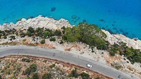 Aerial. White car motion by the mediterranean asphalt road. Vehicle driving with beautiful sea landscape. Top view.  royalty free stock photo