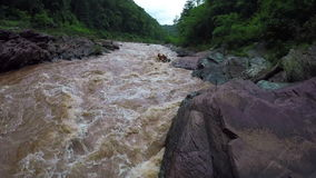 Aerial - Whitewater rafting boat follow shot down river in Thailand.