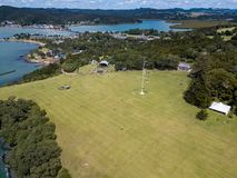 Aerial, Wide Angle Waitangi Day At Treaty Grounds. Crowds gather at waitangi treaty grounds in the bay of islands, aerial view of flag pole Royalty Free Stock Image