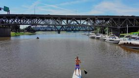 Aerial Flyover View of Man on Stand Up Paddle board on River. An aerial wide flyover view of a man on a stand up paddle board on a Pennsylvania river in the stock video footage